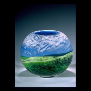 Glass sculpture with grass and blue sky