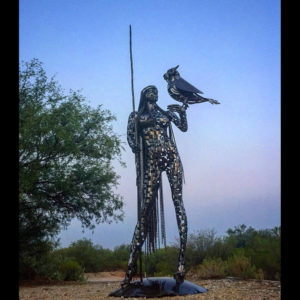 Metal sculpture of a metal lady with a bird