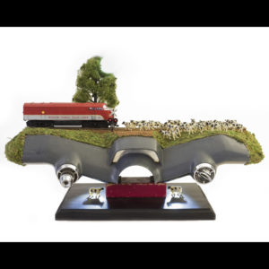 A sculpture with a train, cows, and grass