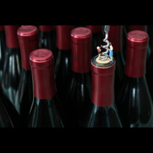 Photograph of bottles of wine with miniature people opening the bottle