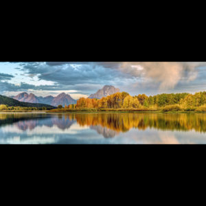 Photograph of a lake in the mountains with aspen trees changing colors